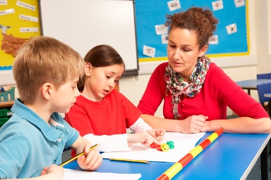 STOCK IMAGE: two children in a classroom with the teacher