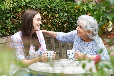 STOCK IMAGE - younger and older woman sat in a garden drinking tea