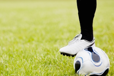 STOCK IMAGE: Football player's leg resting on a football